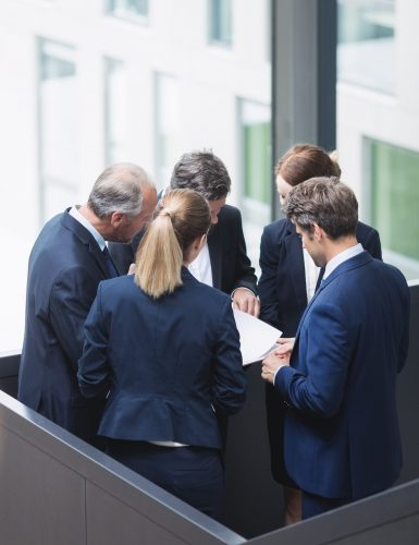 Group of businesspeople having a discussion near staircase in office